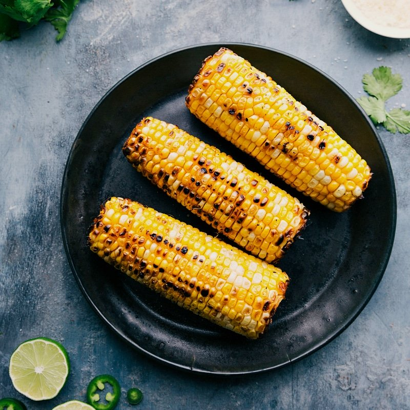 Image of the roasted corn on the cobs on a plate for this pan de elote