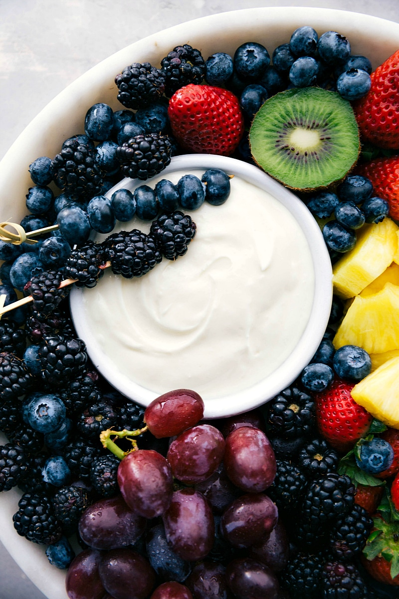 Up-close image of the cream cheese Fruit Dip recipe with a variety of fruit around it.