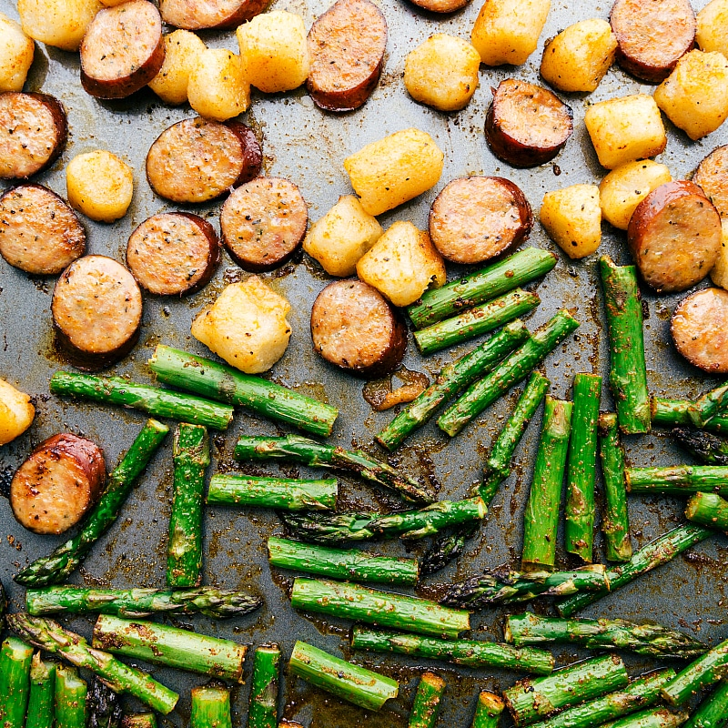 Asparagus is added to sheet pan to go back into the oven; process shot