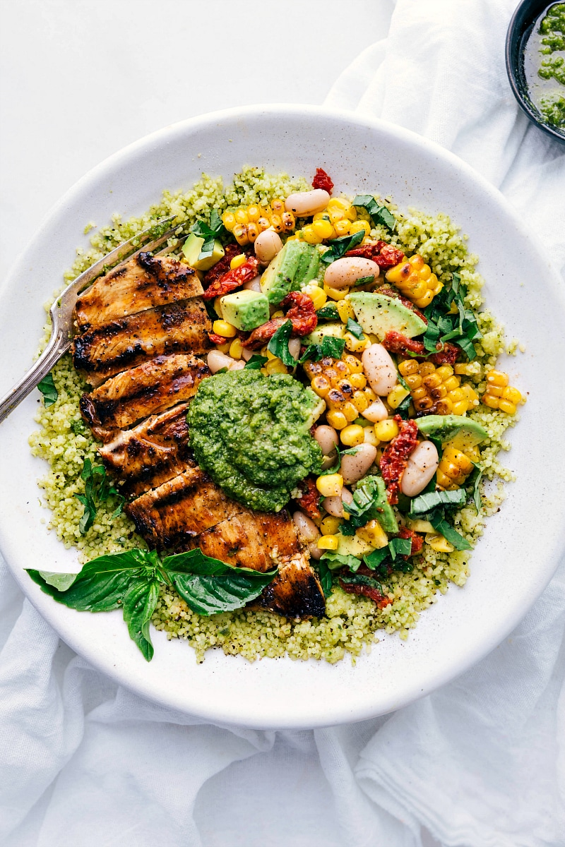Overhead photo of pesto chicken bowls with chicken, corn & white bean salsa, and pesto