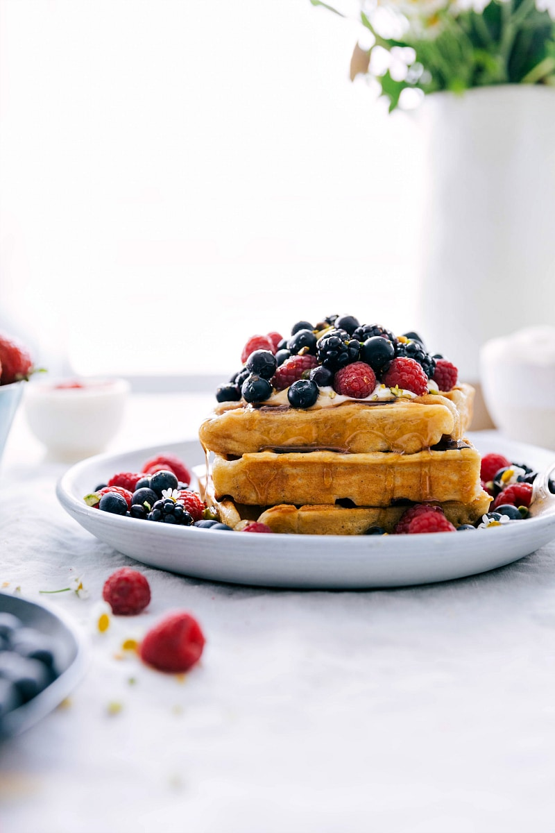 Image of the ready to eat waffle recipe with berries and whipped cream on top with syrup all over.