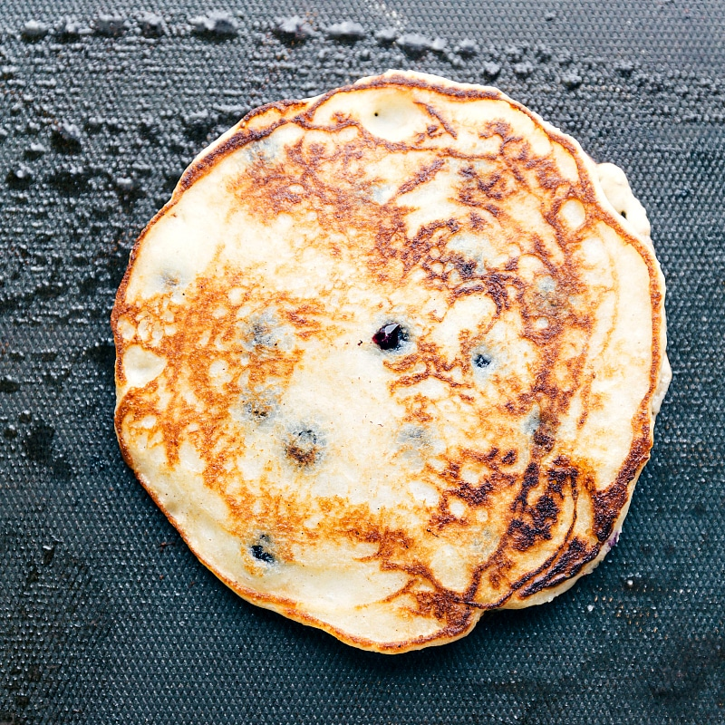 Image of the cooked best blueberry pancake recipe on the griddle still
