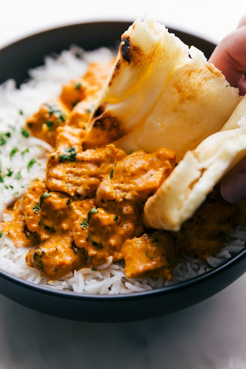 Naan bread scooping up Chicken Tikka Masala over basmati rice.