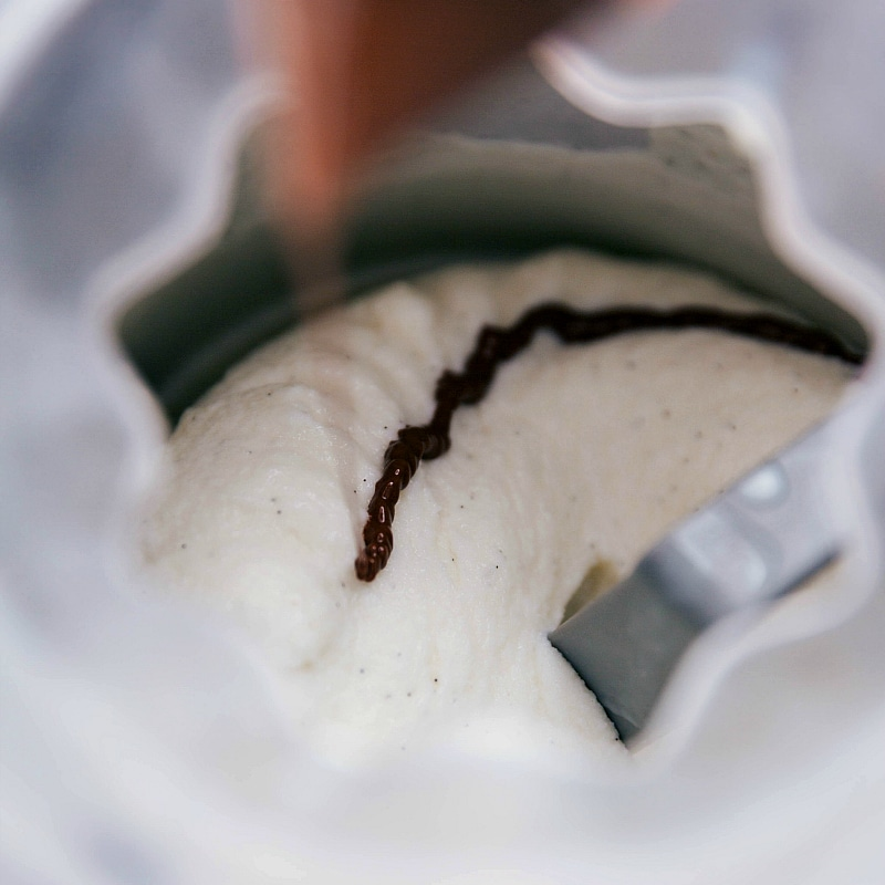 Chocolate being piped into the ice cream maker while churning to make stracciatella.