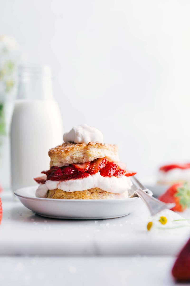 Image of the ready to eat strawberry shortcake with whipped cream on top and a fork on the side of the plate
