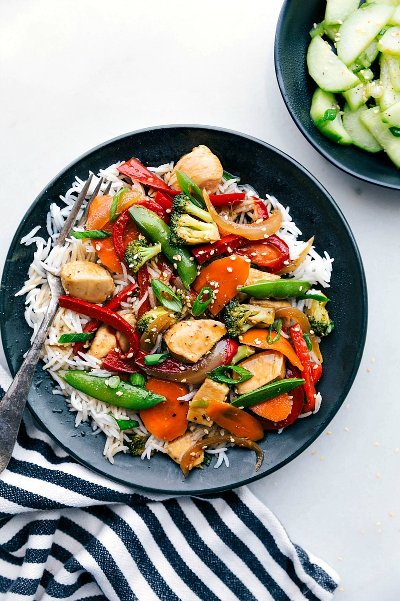 Image of the chicken stir fry recipe in a bowl with rice and a fork on the side