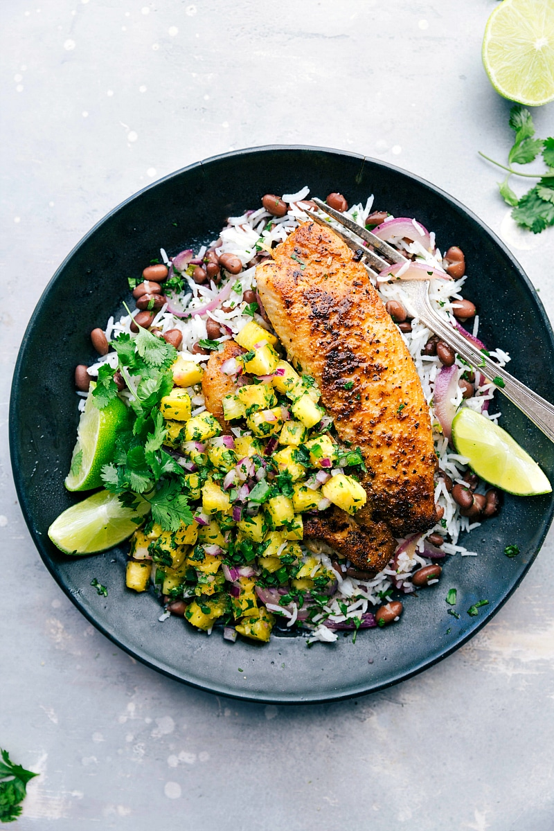 Overhead image of the blackened tilapia on a plate with pineapple salsa, rice, and black beans