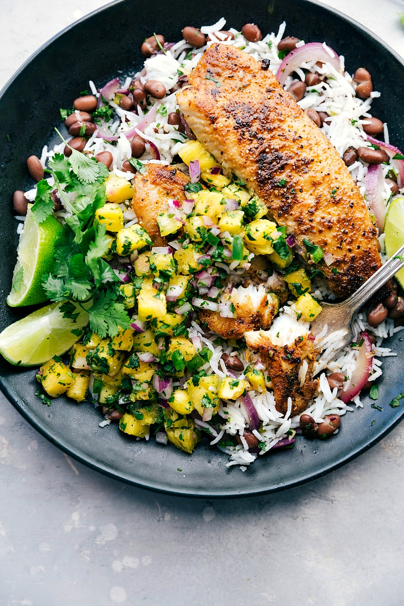 Image of Blackened Tilapia, pineapple salsa, and rice base with a bite out of it.