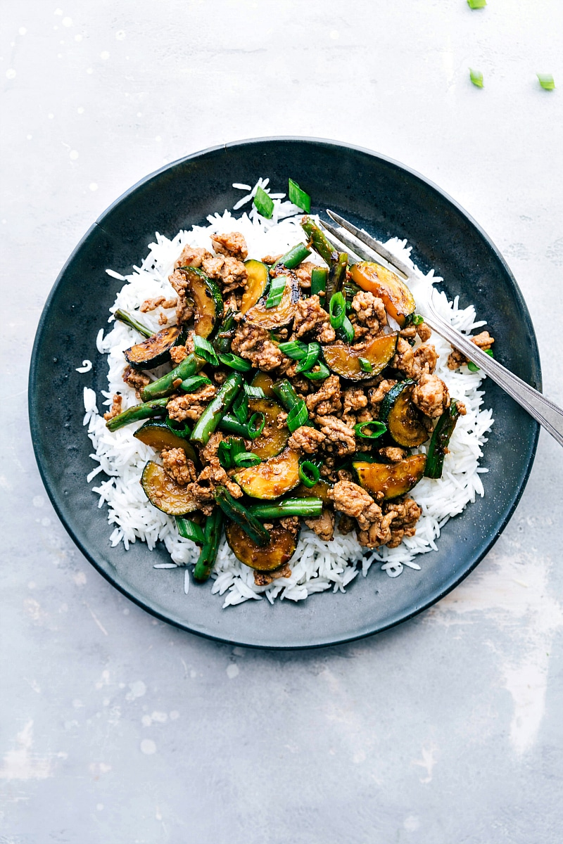 Overhead image of Pork Stir Fry over rice, with a fork on the side, ready to eat.