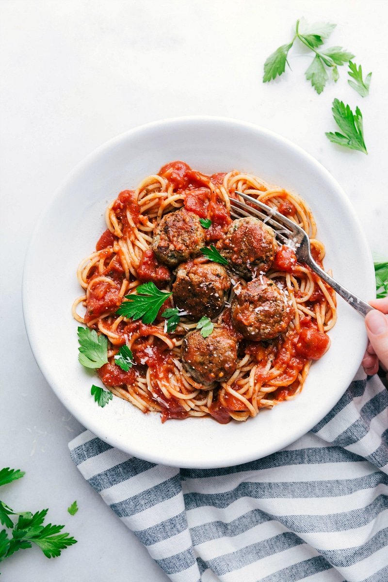 Bowl of finished turkey meatballs over spaghetti with sauce. Hand holding a fork ready to dig in
