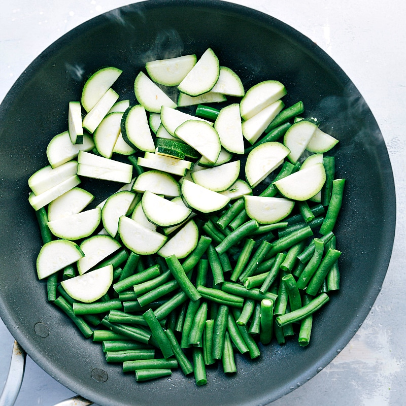 Image of the uncooked zucchini and green beans in the skillet about to be sautéed