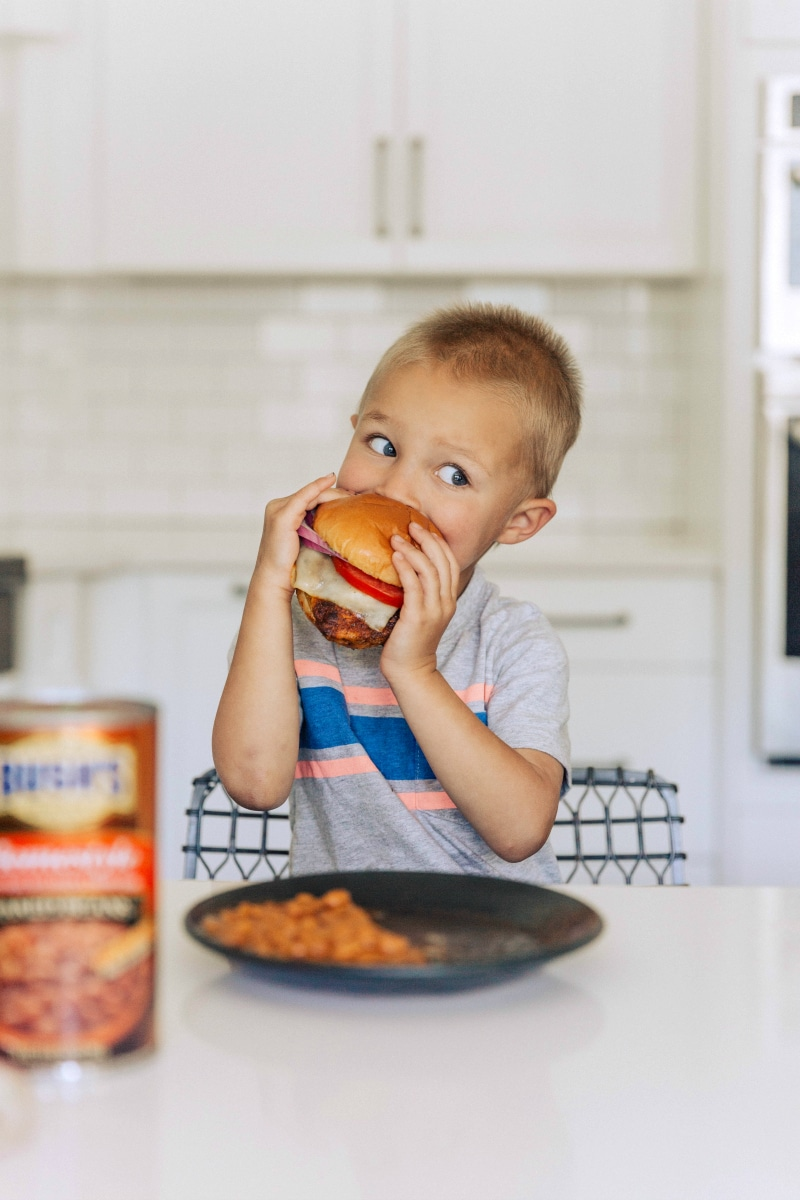 Image of a little boy eating the chicken burger