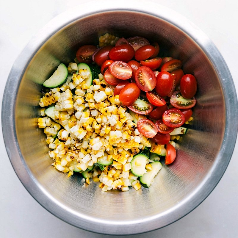 Process shot-- Image of the corn and zucchini salad in a bowl about to be mixed