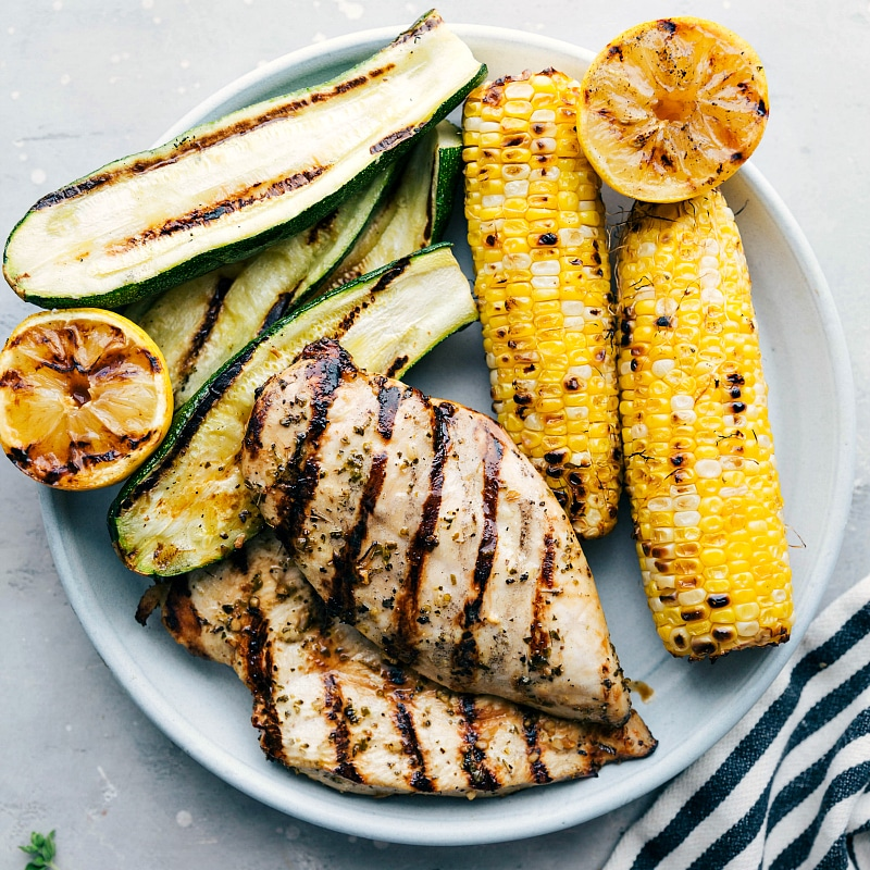 Overhead image of the greek chicken with grilled zucchini, corn, and lemons on the side