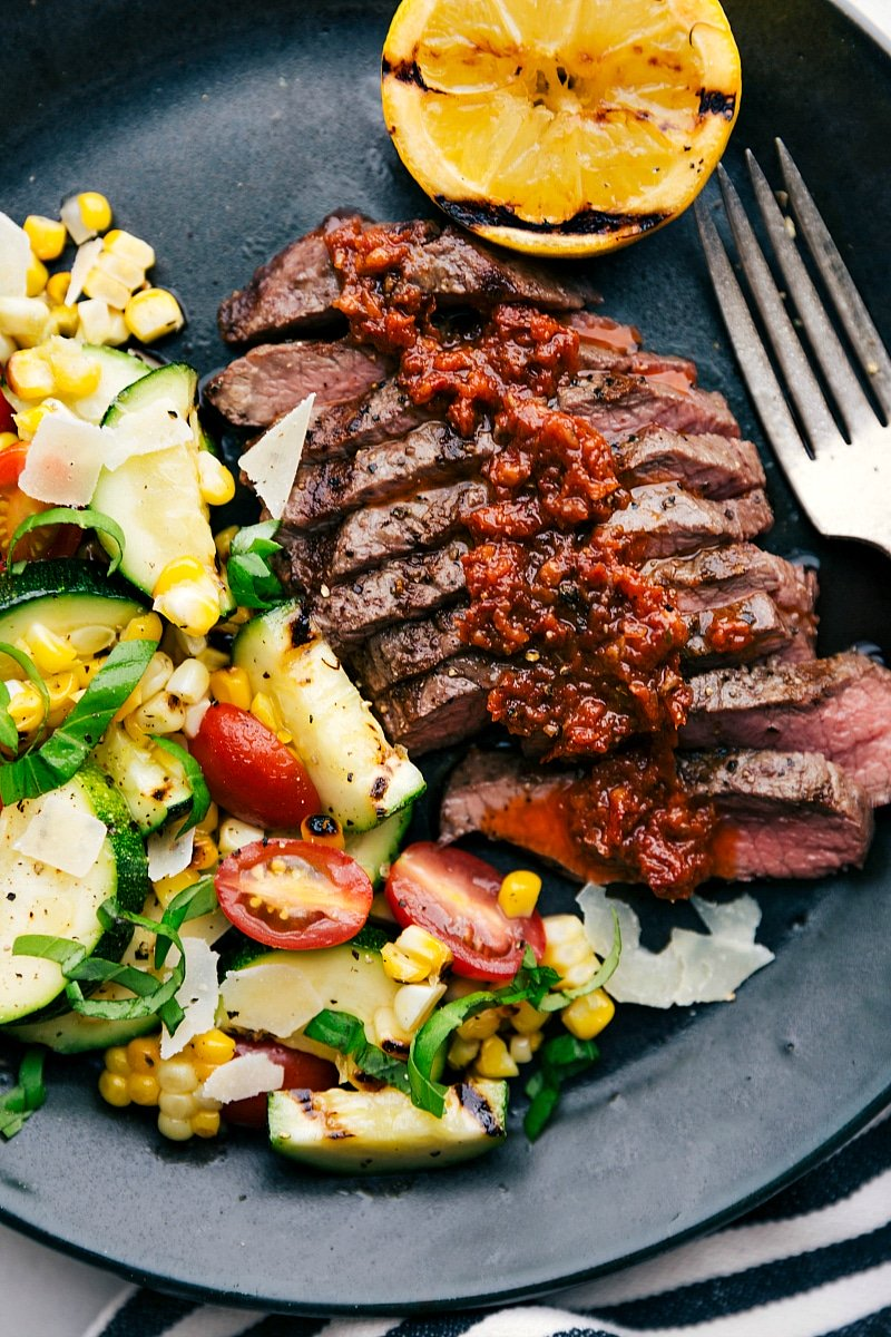 Up close image of the grilled flat iron steak with the grilled corn and zucchini salad on the side
