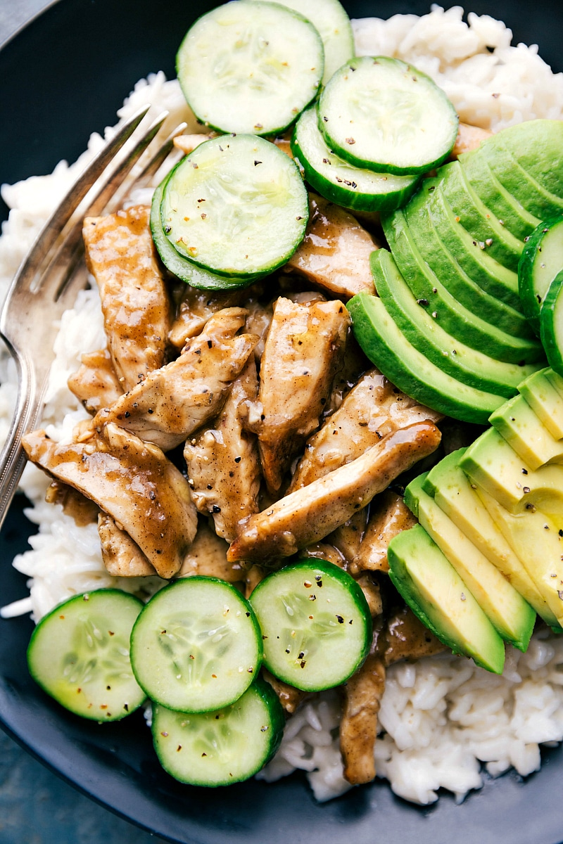 Up close image of the apricot chicken with avocado and cucumbers on the side on a bed of rice