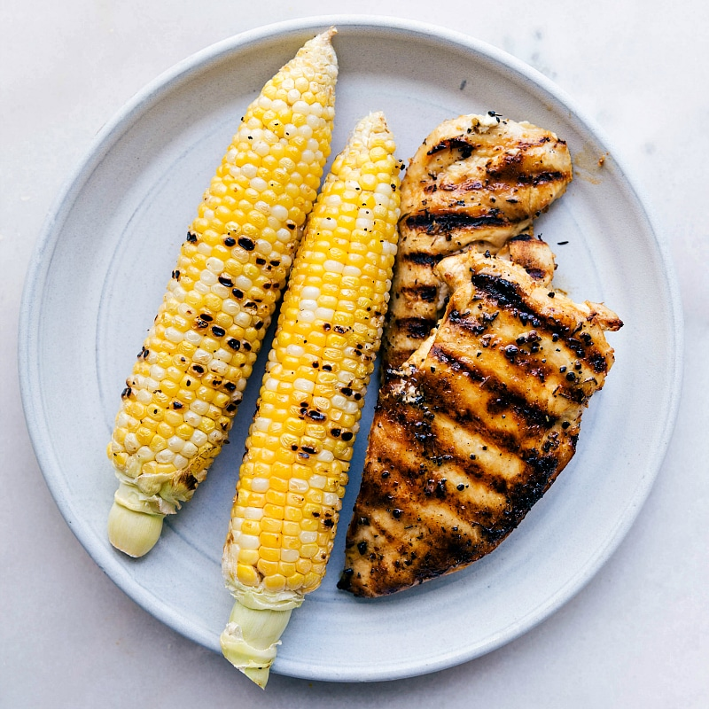 Overhead image of the corn and chicken on a plate, freshly grilled.