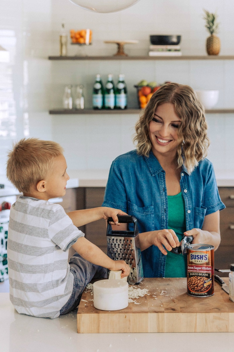 Image of Chelsea and her son opening a can of beans for this chicken Alfredo bake