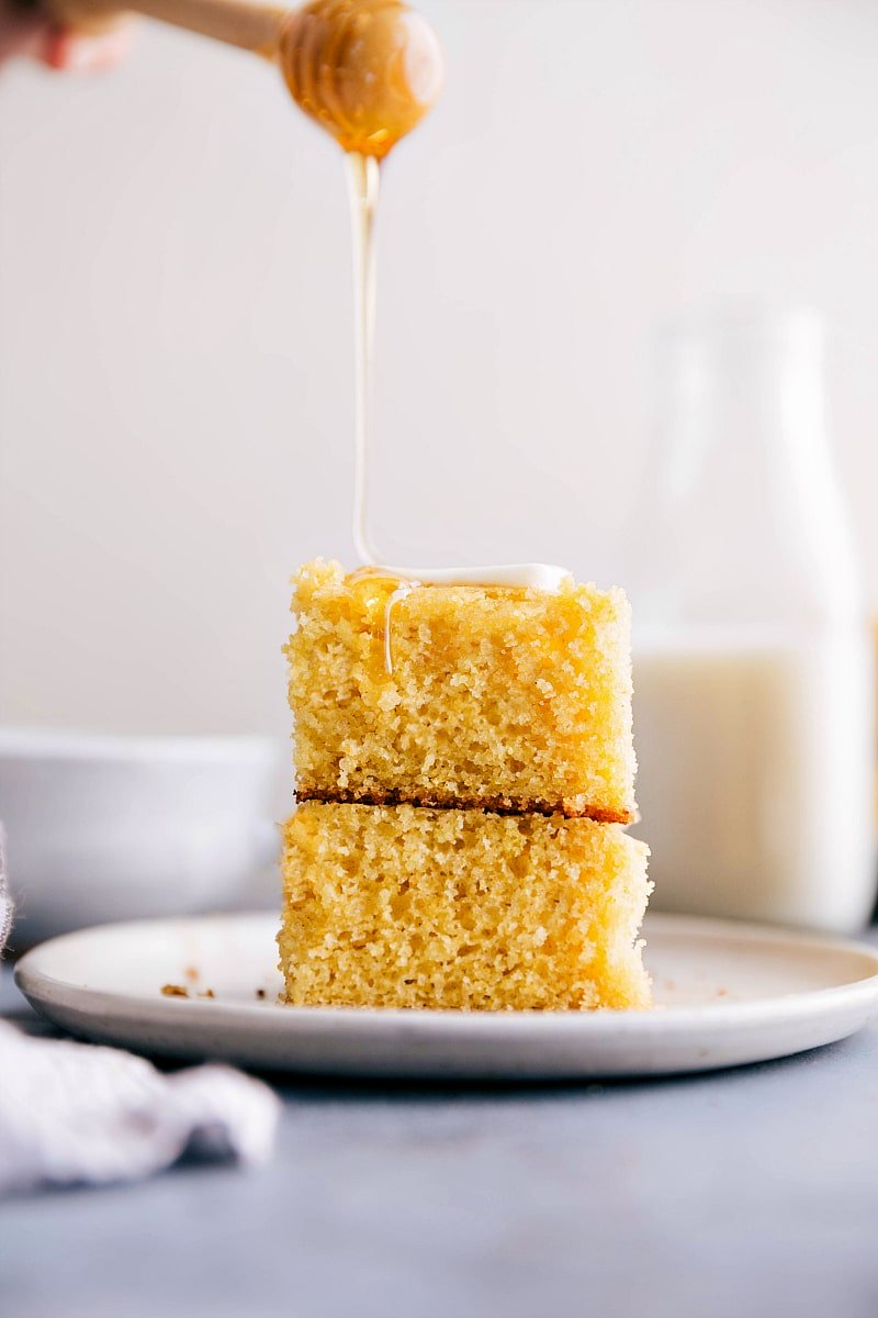 Image of two slices of cornbread stacked on top of each other with honey being poured on top