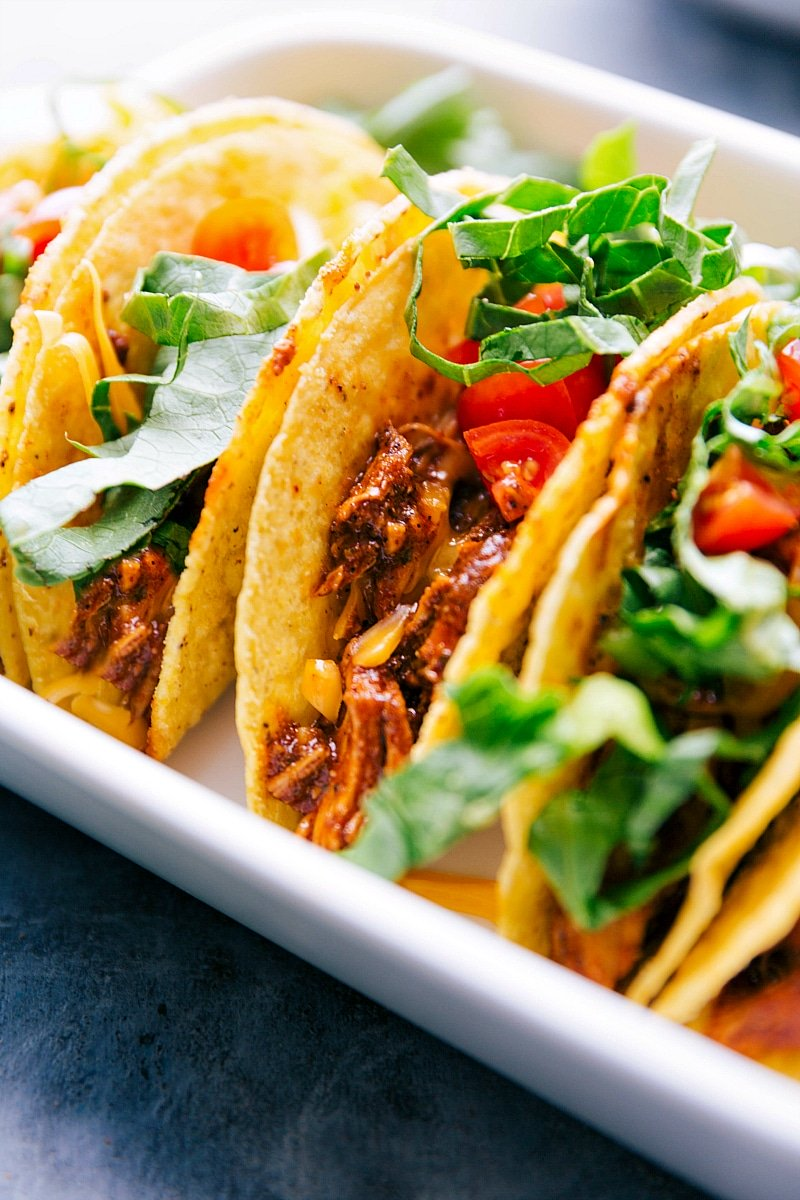 Up close image of Rotisserie Chicken Tacos with toppings on, ready to be eaten.