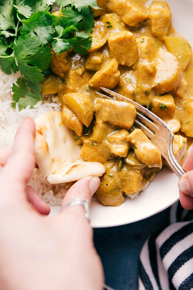 Overhead image of the yellow chicken curry being scooped onto a naan bread ready to be eaten