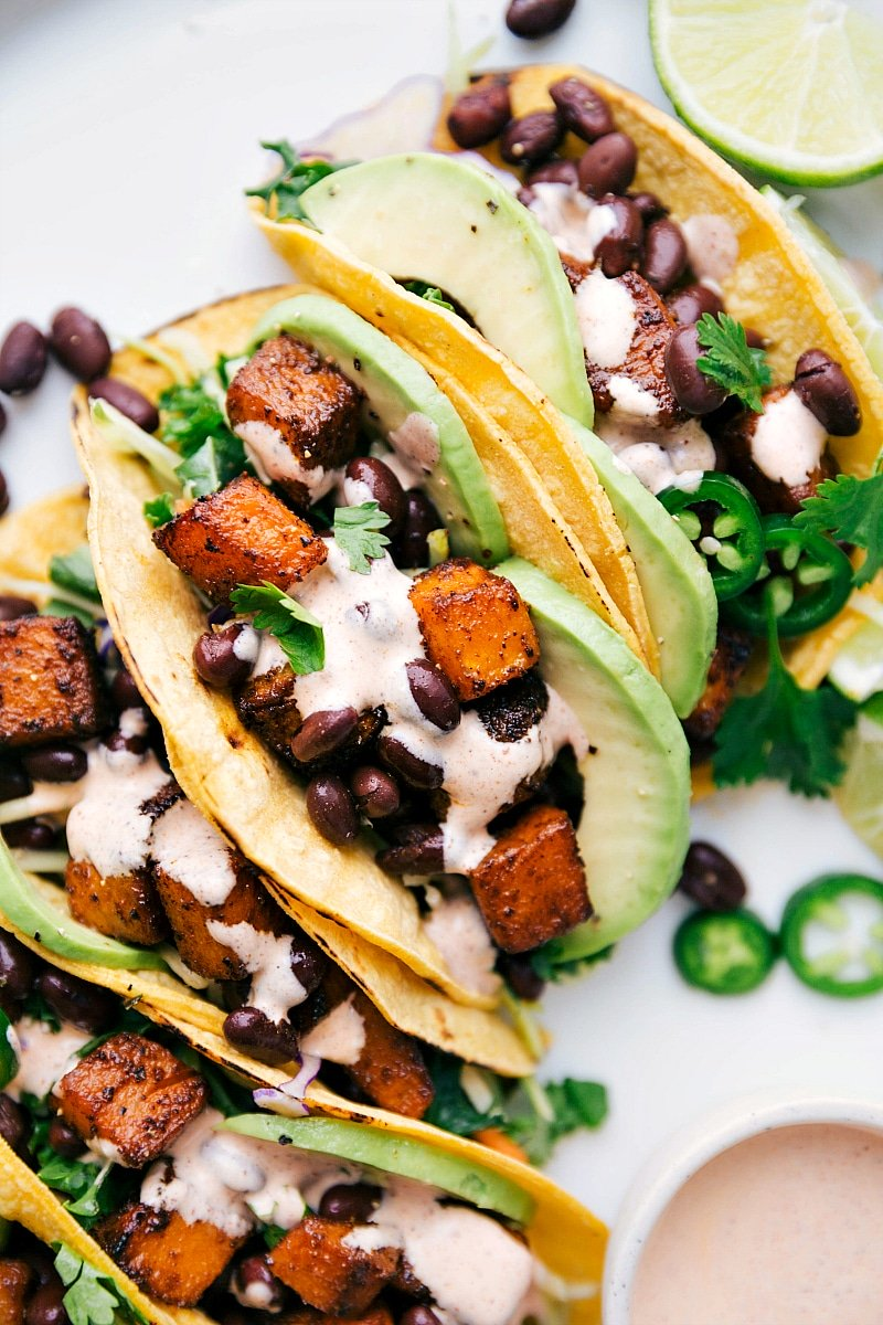 Overhead image of Butternut Squash Tacos with dressing and toppings, ready to be served