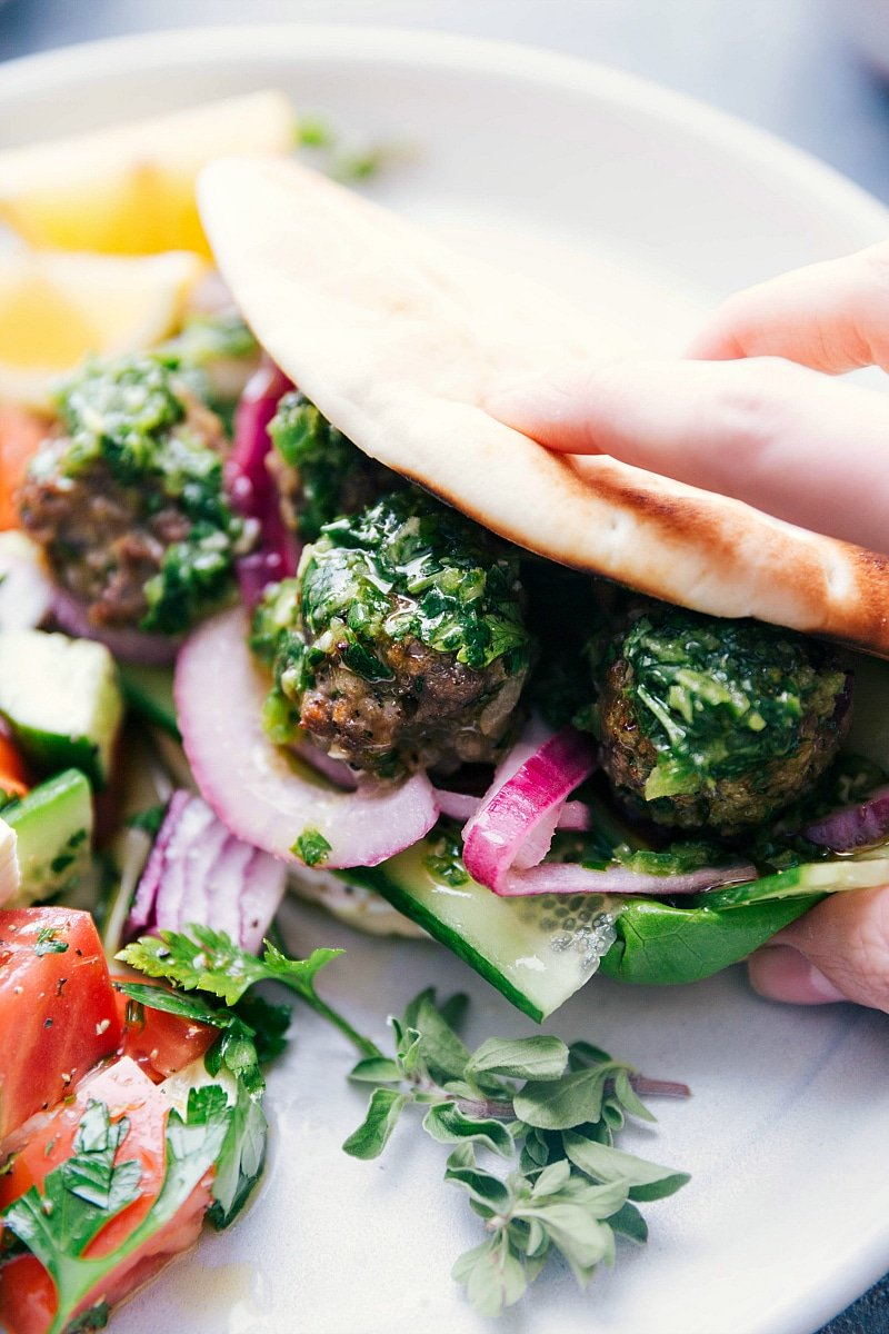 Image of the greek meatballs being served in a pita with toppings and sauce ready to be eaten