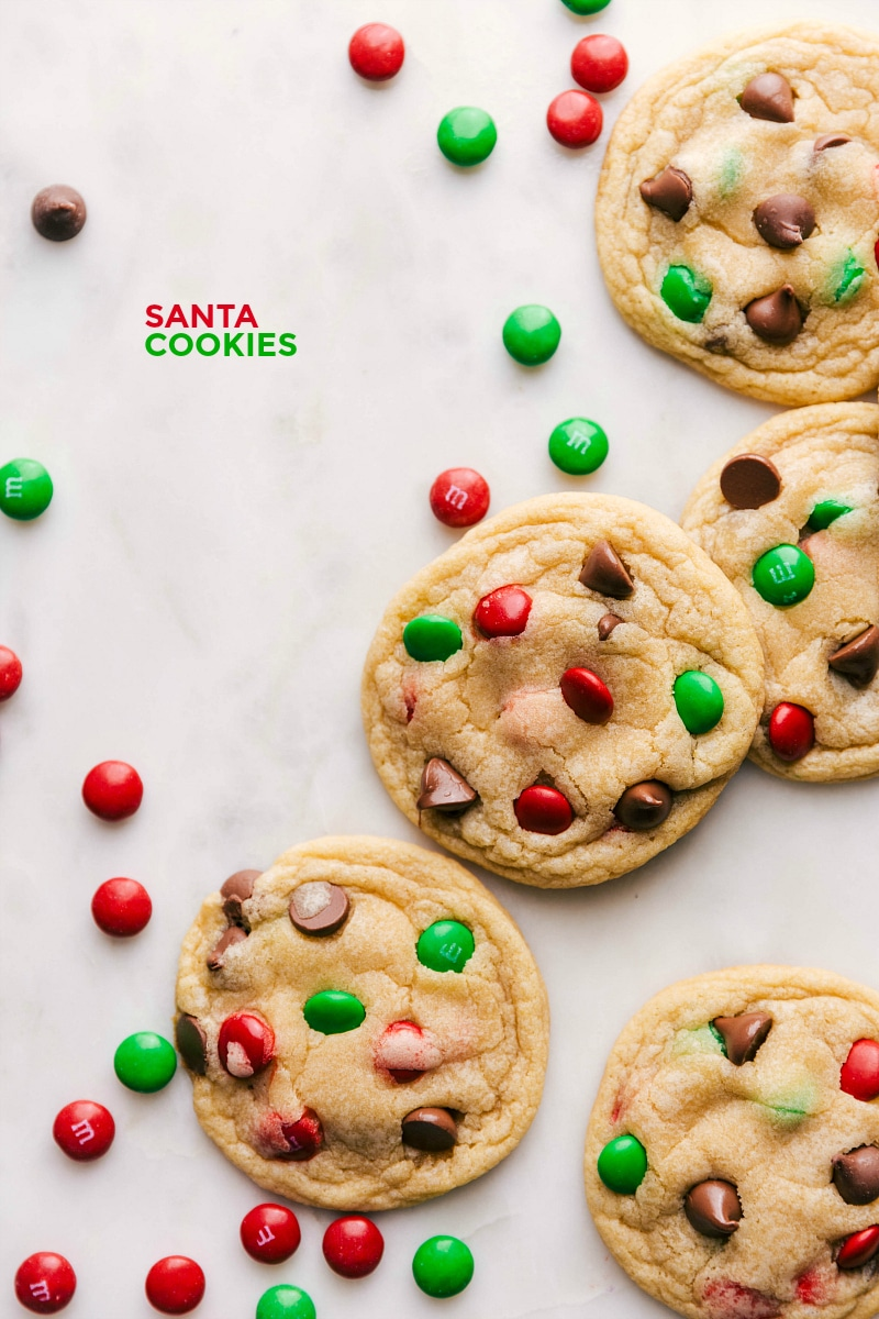 Overhead image of several Santa Cookies, surrounded by red and green candies.