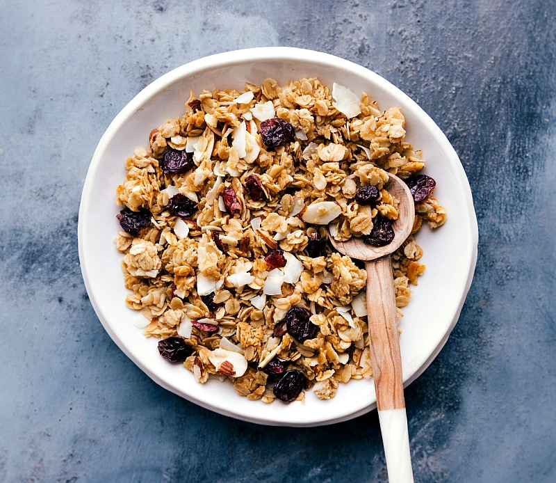 Image of Almond Granola in a bowl with a spoon in it.