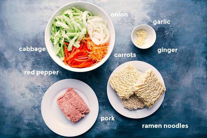 Ingredient shot listing everything in this Egg Roll Noodle recipe -- cabbage, red pepper, onion, carrots, ramen noodles, ground pork, garlic, and ginger