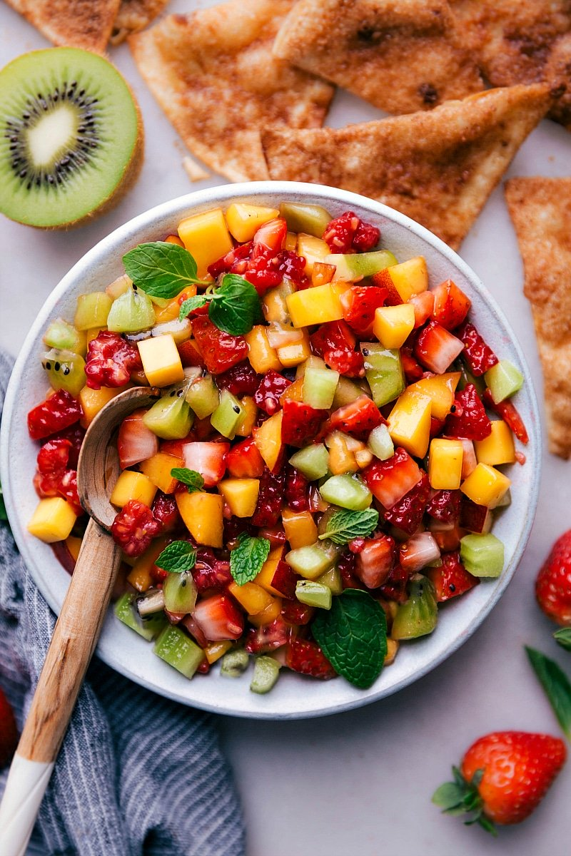 Overhead image of fresh Fruit Salsa in a bowl with a spoon in it and cinnamon tortillas on the side.