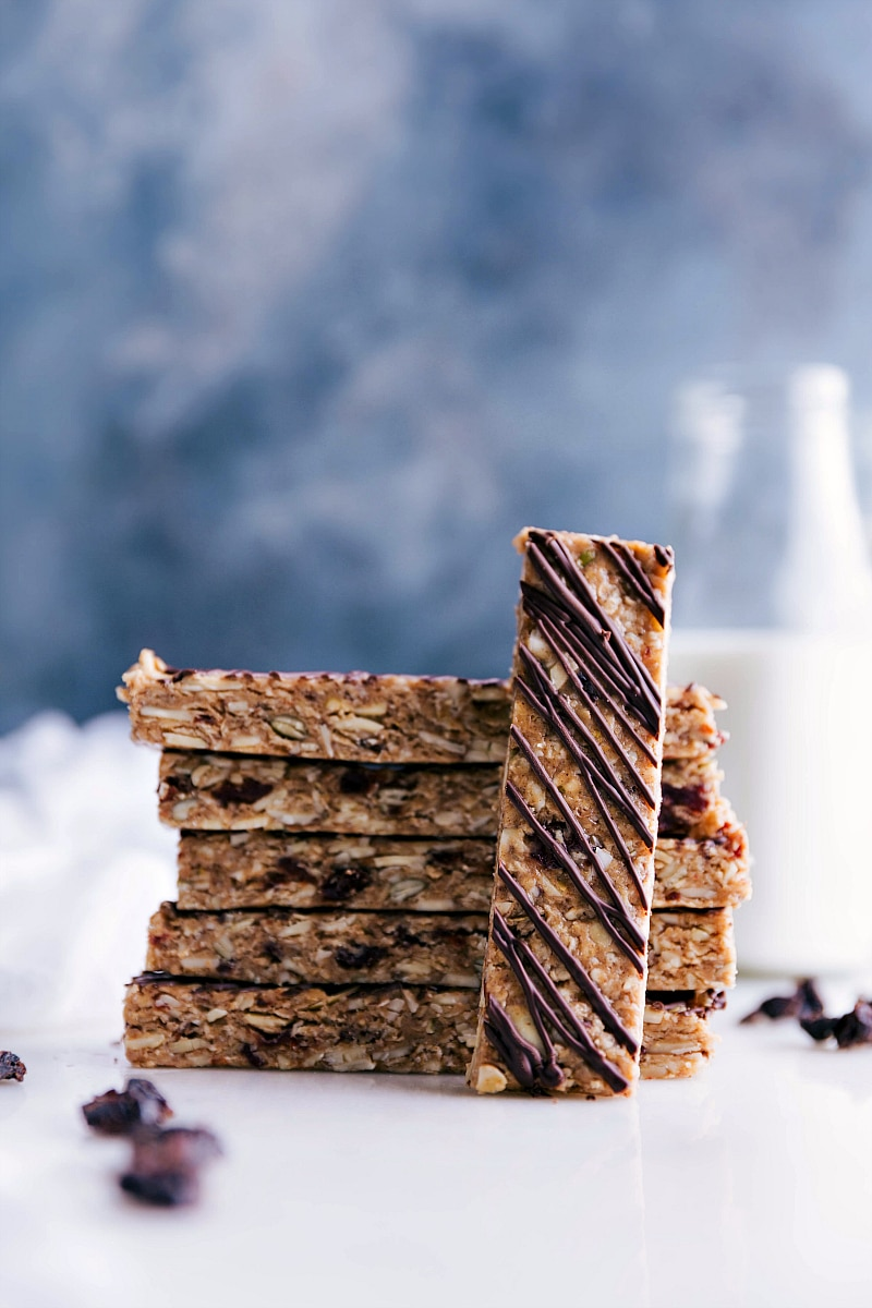 Image of the no bake granola bars stacked on top of each other with one laying on the side of the stacked ones