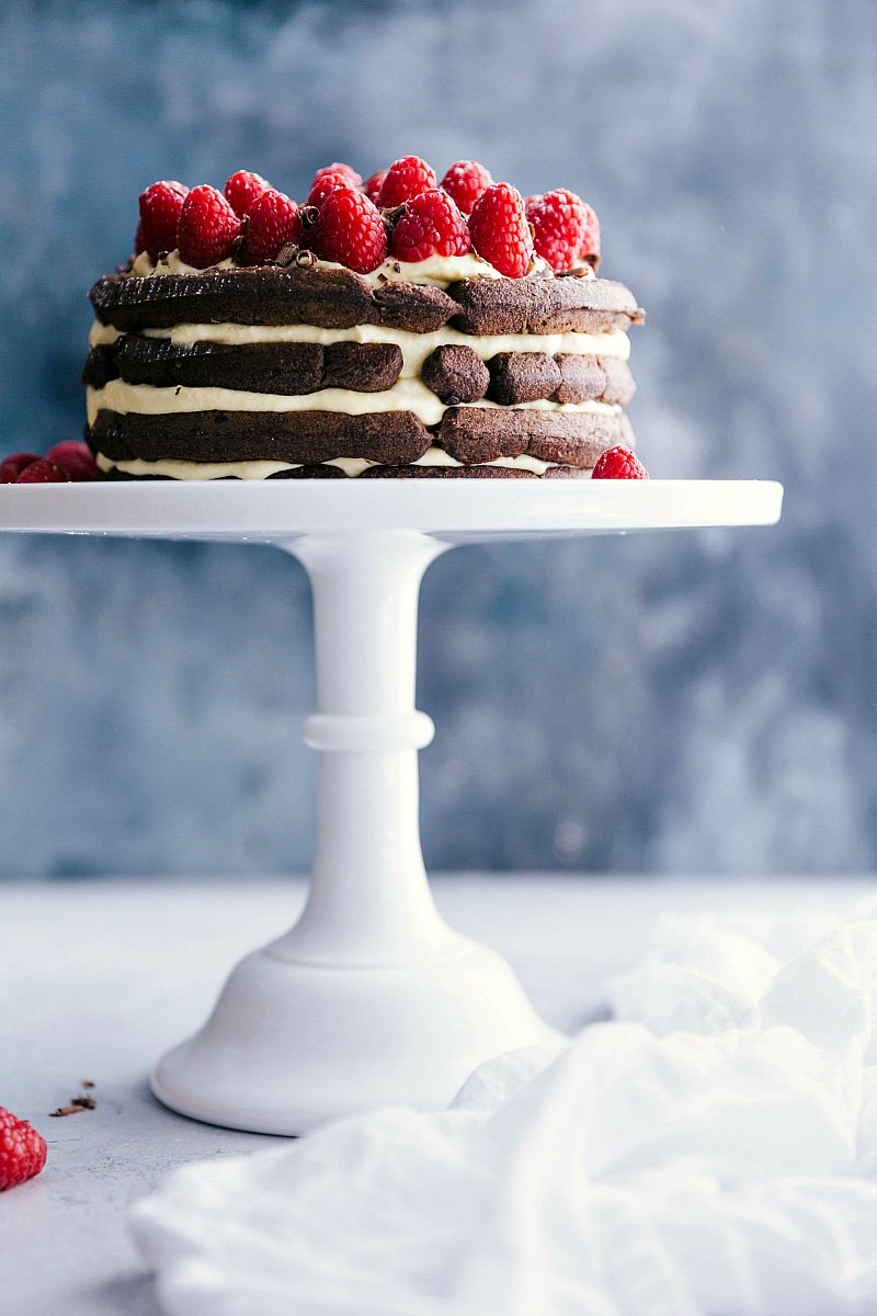 Image of the waffle cake on a cake stand with fresh raspberries on top ready to be eaten
