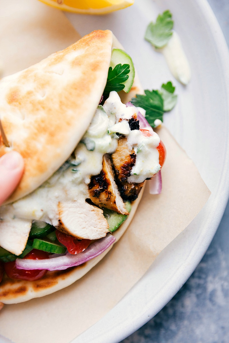 Overhead image of Chicken Gyros in a pita with the tzatziki sauce spilling out, ready to be eaten.