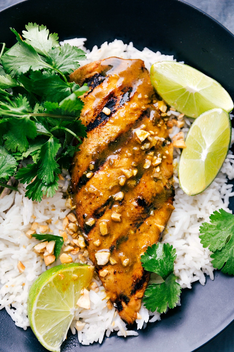 Up-close overhead image of Grilled Curry Chicken over coconut rice with fresh lime wedges and cilantro on the side.