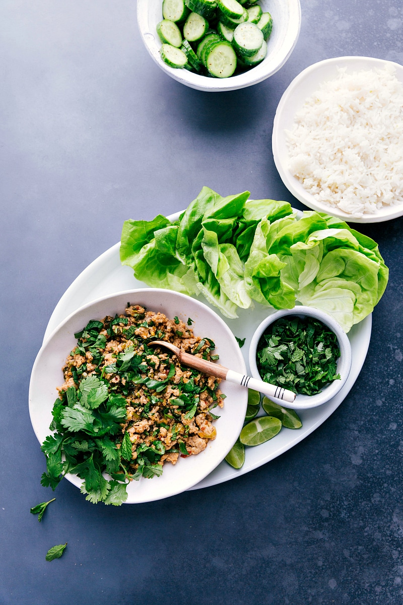 Overhead view of Chicken Larb on a platter, with a plate of rice and a bowl of sliced cucumbers to accompany.
