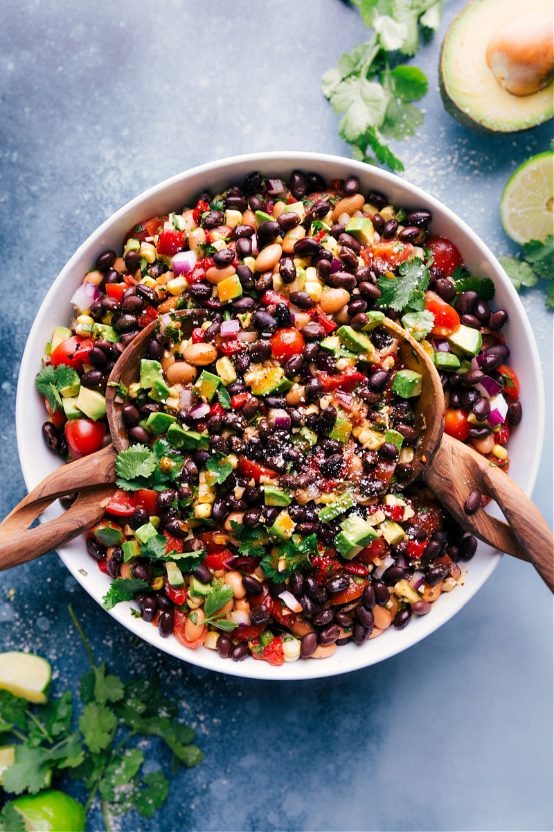 Overhead view of Cowboy Caviar in a serving bowl, with wooden serving spoons.