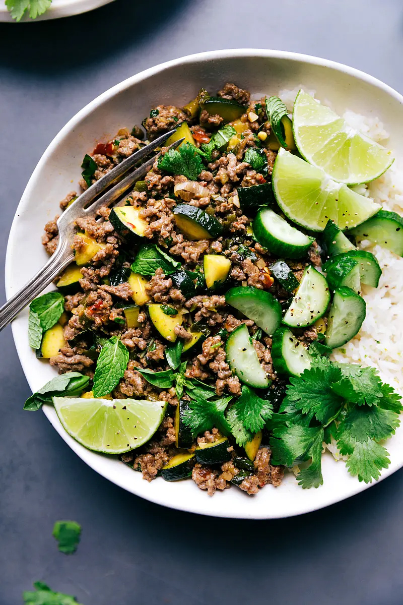 Photo of Beef Larb, rice and garnishes of lime and cilantro.