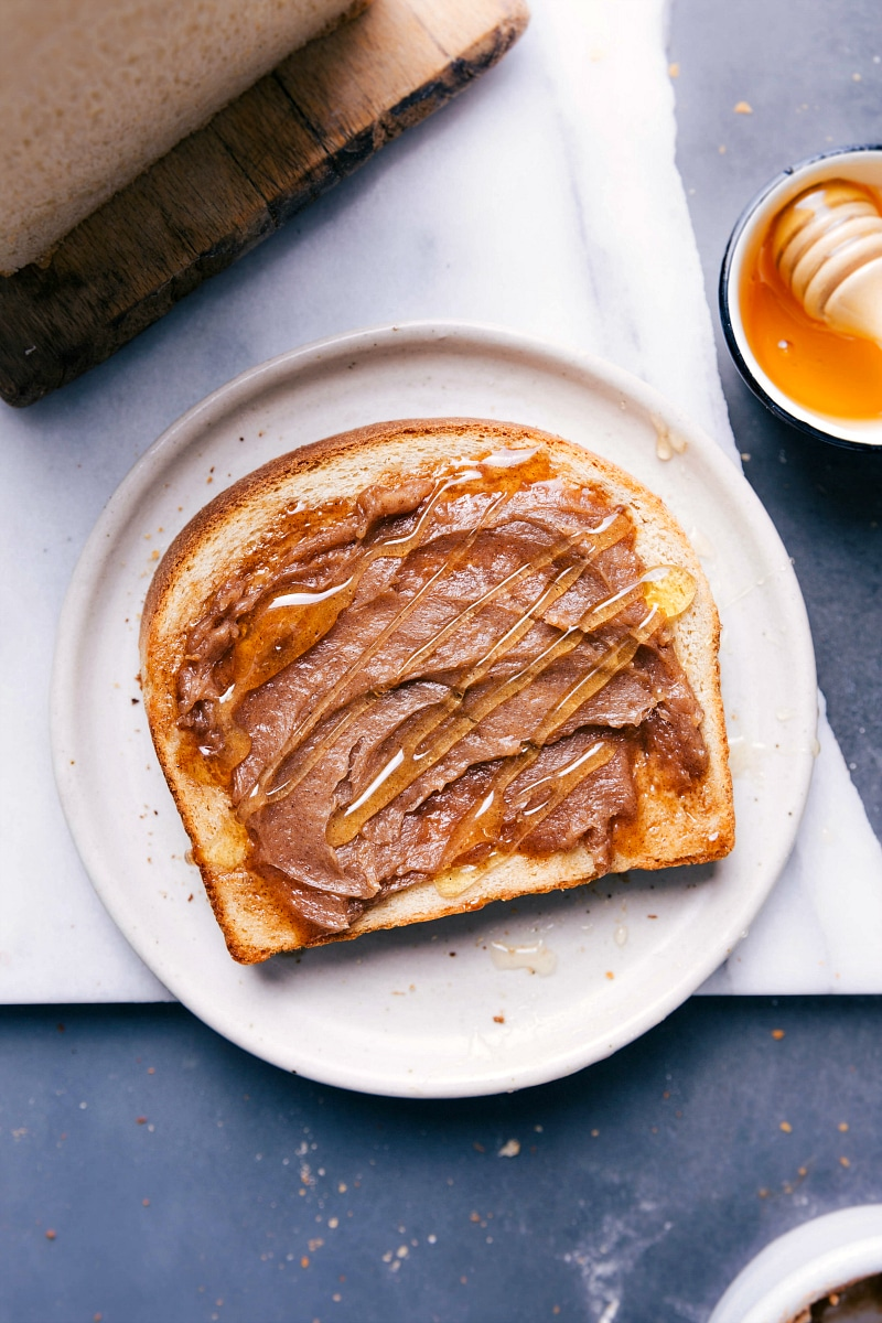 Overhead image of a slice of bread with fresh honey and honey butter on it.