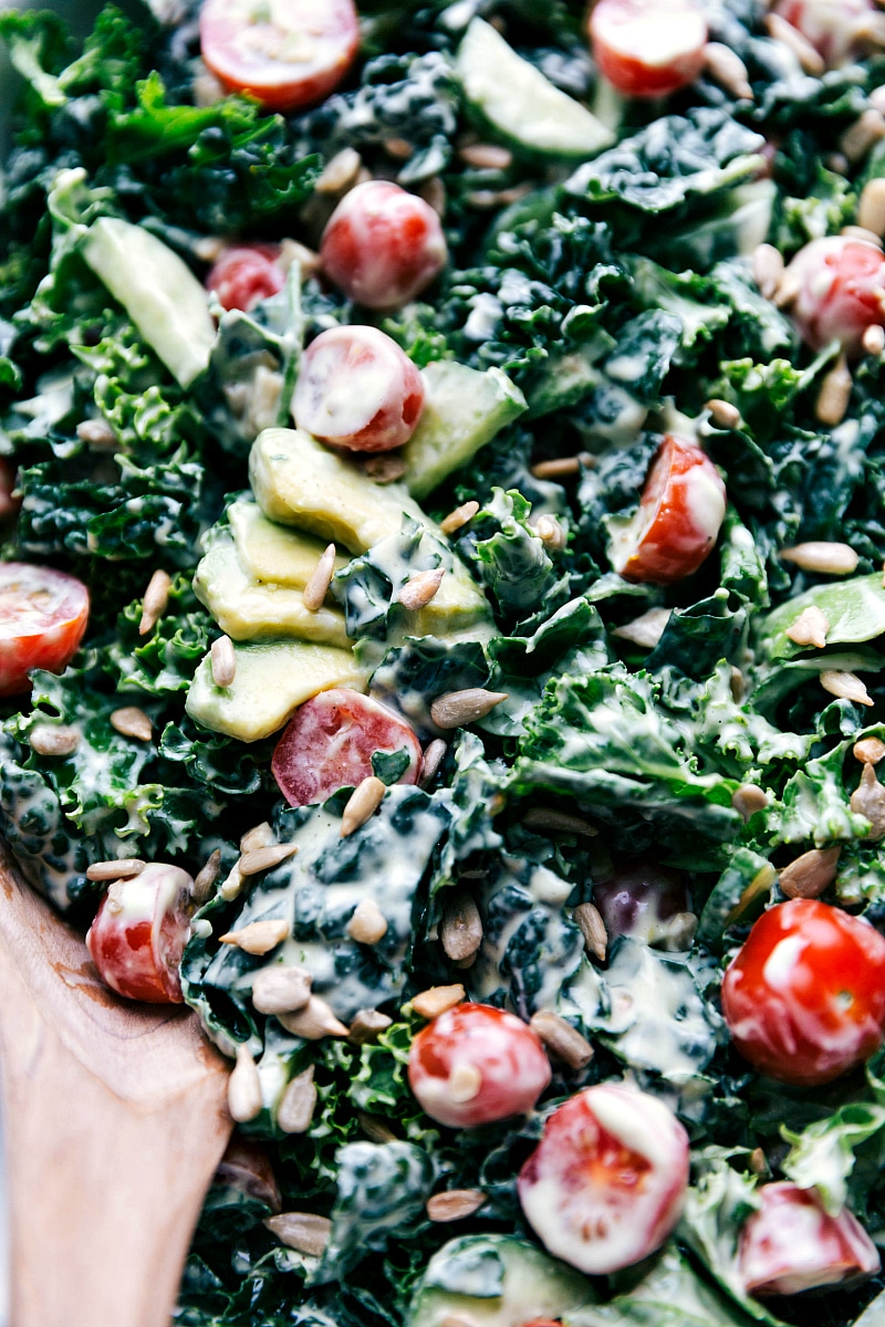 Overhead image of Kale Avocado Salad with a wooden spoon in it.