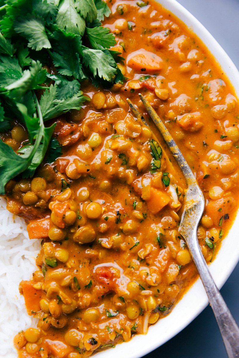 Overhead image of Lentil Curry with a fork beside it, and fresh cilantro and rice on the side.