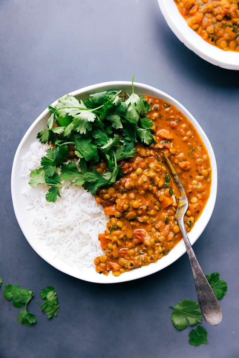 Overhead image of Lentil Curry in a bowl, with t.he rice on the side and fresh cilantro on top