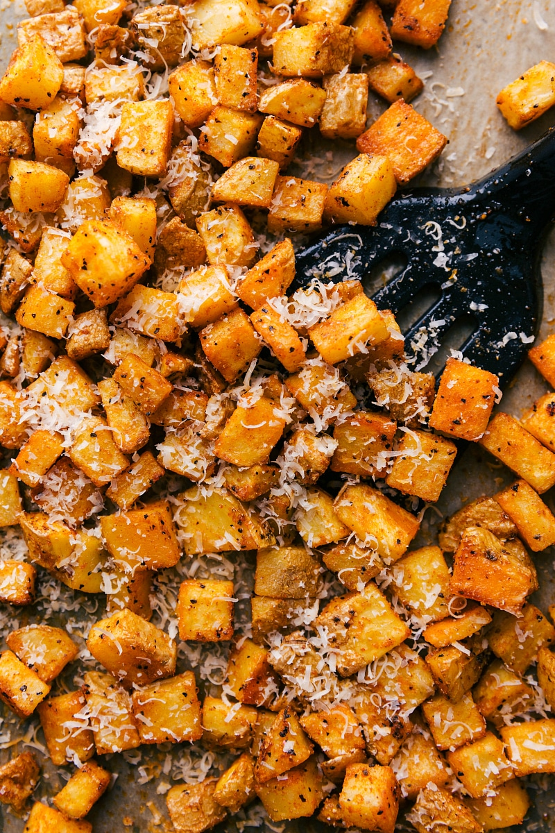 Overhead image of roasted potatoes being scooped up with a spatula.