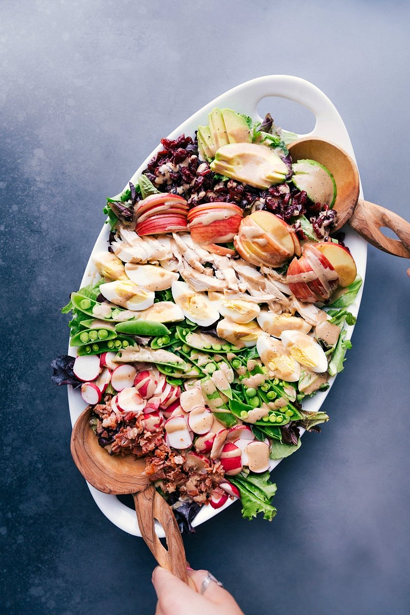 Overhead view of a large serving platter filled with Cobb salad, featuring meats, veggies, fruit and Creamy Balsamic Dressing.