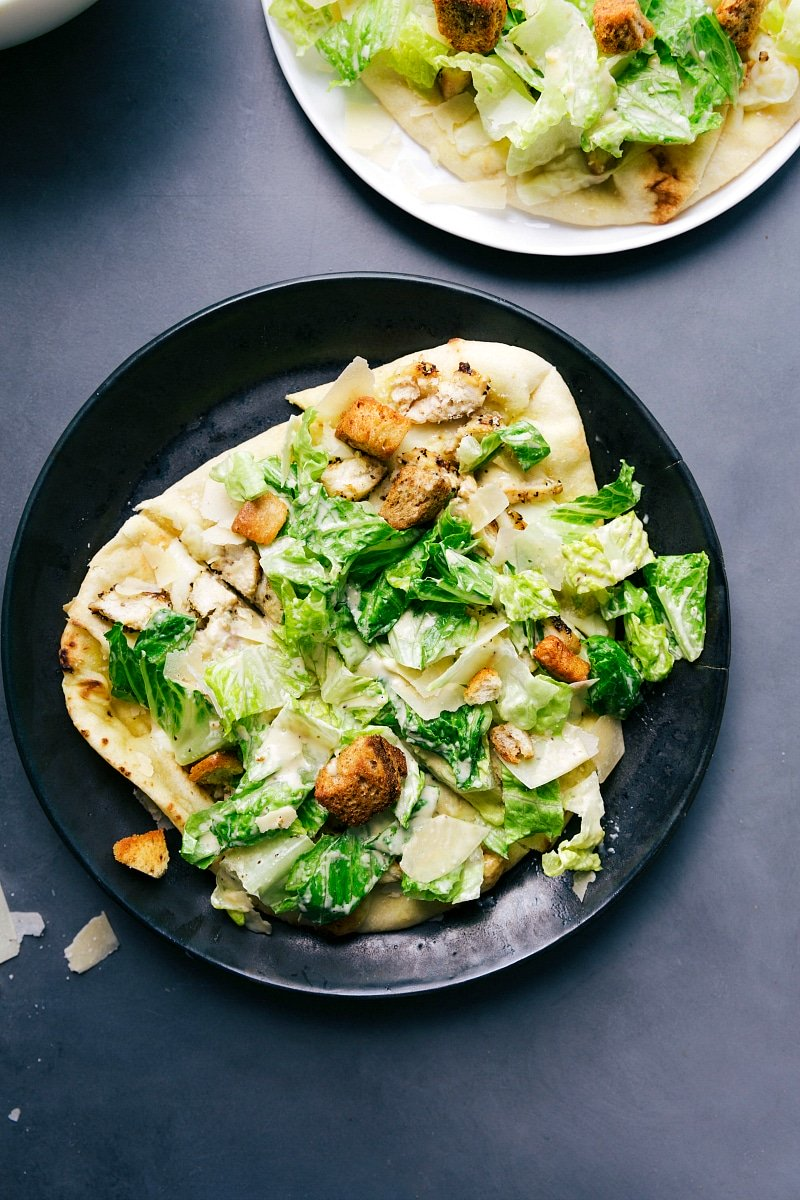 Overhead image of Caesar Salad Pizza cut up and ready to be eaten.