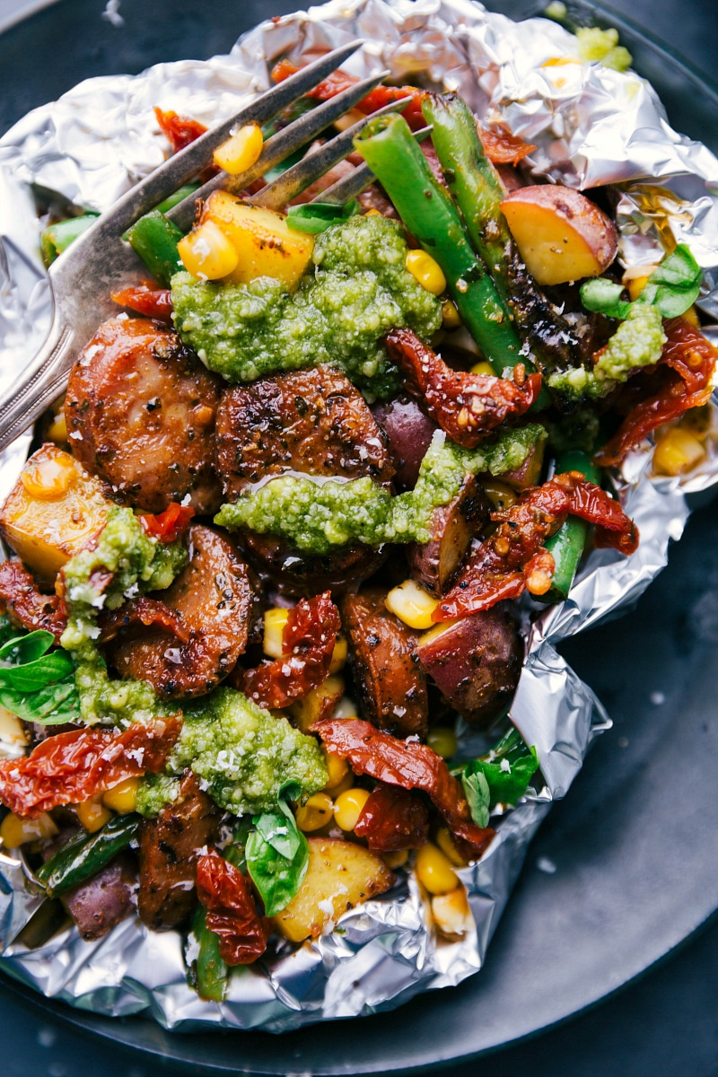 Up-close overhead image of the foil pack dinner with fresh pesto on top and a fork in it.