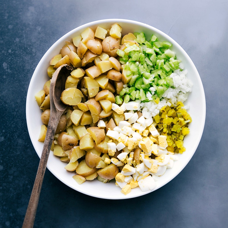 Overhead view of the ingredients: cooked and chopped Yukon gold potatoes, diced celery, onion, hard-boiled eggs and pickles.