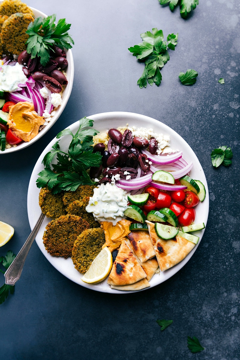 Overhead image of Falafel in a bowl with pita bread, tzatziki sauce, olives, onions, tomatoes, and cucumbers.