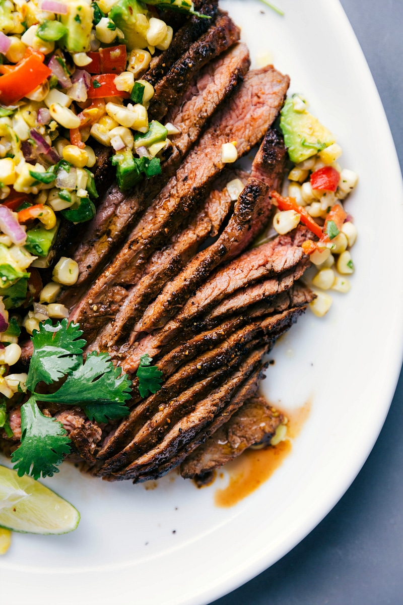 Up-close overhead image of sliced Flank Steak with Corn Salsa about to be eaten.
