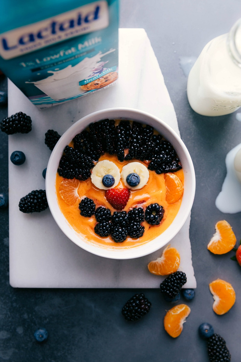 Overhead image of the peach smoothie bowl with an Ernie face
